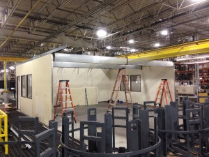 Installing the reconfigured in-plant office in its new location. Recessed beams used to support the roof deck due to the long spans.