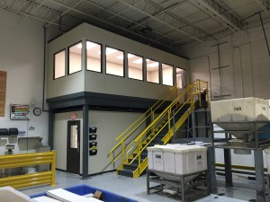 Modular wall system above and below a mezzanine