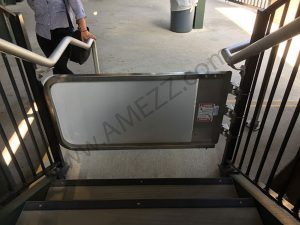Rear view of MLG 304 stainless steel safety gate mounted to stairs with pedestrian traffic control sign.